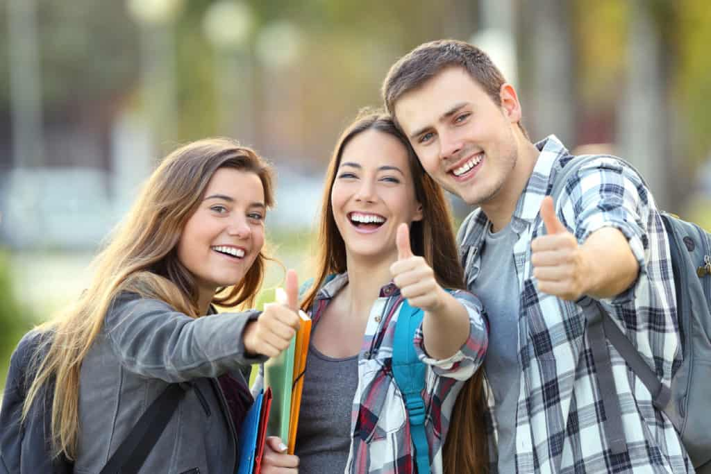 Three happy students looking at you with thumbs up in an university campus