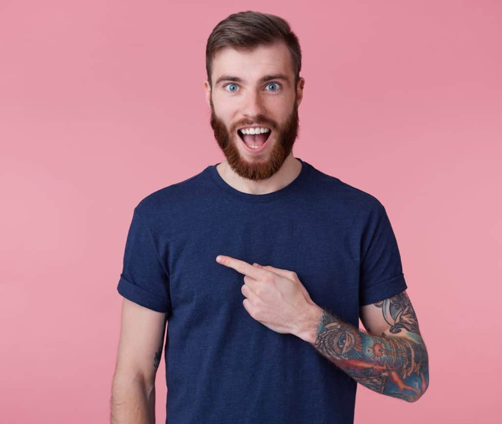 Young happy amazed attractive red-bearded young guy , wearing a blue t-shirt, with wide open mouth in surprise, pointing finger to copy space at the left side isolated over pink background.